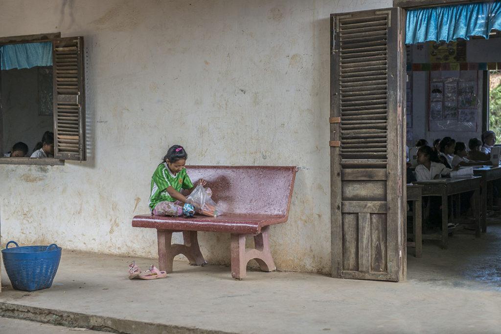 Flicka, vars föräldrar inte har råd att låta henne gå i skolan, leker med sin docka medan hon väntar på sina kamrater Foto: Johan Bünger